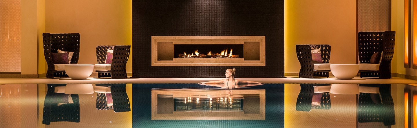 A young woman bathes in the swimming pool with fireplace and relaxation area of ​​the Severin*s Resort and Spa on Sylt